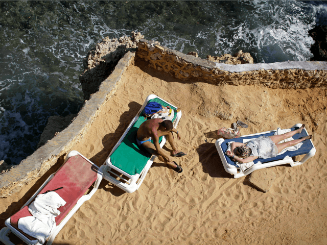ourists sunbathe on the shore of the Red Sea at a hotel that is hosting many travelers waiting to be evacuated from the resort city of Sharm el-Sheikh, south Sinai, Egypt, Saturday, Nov. 7, 2015. Russia has suspended all flights to Egypt, joining the U.K., which had specifically banned all …