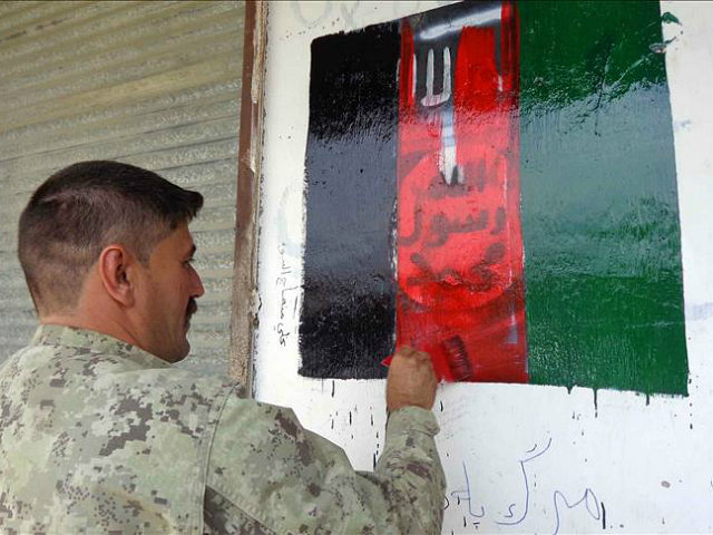 NANGARHAR, AFGHANISTAN - AUGUST 01: An Afghani soldier paints an Afghan flag on a wall after they retook Nangarhar's Kot district from the terrorist organization Daesh in Nangarhar's Kot district, Afghanistan on August 01, 2016. (Photo by Zabihullah Ghazi /Anadolu Agency/Getty Images)