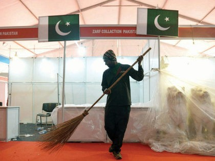 An Indian sweeper cleans the red carpet in the front of Pakistani flags which were on display at the Pakistan stalls during the Punjab International Trade Expo PHD (PITEX) 2016 Trade Fair in Amritsar on December 10, 2016. Narinder NANU / AFP