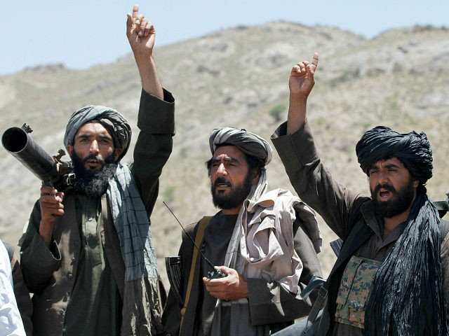FILE - In this May 27, 2016 file photo, Taliban fighters react to a speech by their senior leader in the Shindand district of Herat province, Afghanistan. Two senior Taliban figures said that Pakistan has issued a stark warning to the militant group, apparently surprised over being excluded from the insurgents' secret talks with the Afghan government. (AP Photos/Allauddin Khan, File)