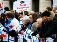 "Pro-Israel demonstrators hold a placard reading ""United Nations Organization Disproportionate Focus on Israel"" during a gathering in front of Israel embassy in Paris, France, Sunday, Jan. 15, 2017. Fearing a new eruption of violence in the Middle East, more than 70 world diplomats gathered in Paris on Sunday to push …"