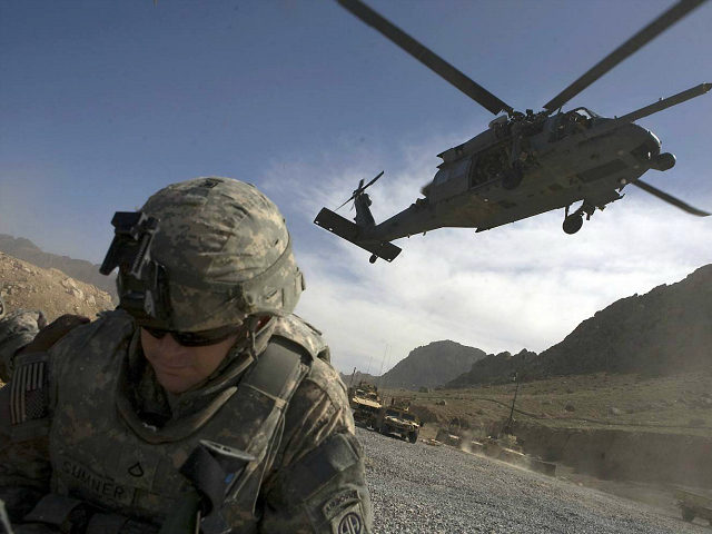 A U.S. soldier with 4th Brigade combat team, 2-508, 82nd parachute infantry Regiment waits for a Black Hawk helicopter to land in the Arghandab valley in Kandahar province, southern Afghanistan, February 20, 2010. REUTERS/Baz Ratner