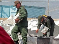 A member of the National Guard looks after 2.6 tons of cocaine seized in Maracaibo, Zulia state, northwest of Venezuela, on April 25, 2013. According to the minister of Interior and Justice, Miguel Rodriguez, the drug was to be sent to Honduras. AFP PHOTO/Jimmy Pirela (Photo credit should read JIMMY …