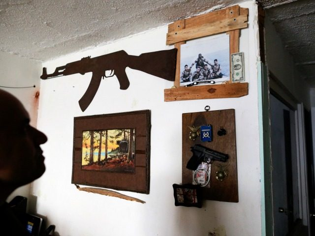 In this Feb. 13, 2017 photo, U.S. Marine veteran Antonio Romo looks at a replica of a pistol and other military items from his time in the service, mounted on his apartment wall in Tijuana, Mexico. Romo, who says he turned to alcohol and narcotics to try to quiet his …