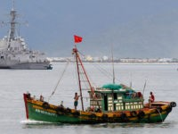 A Vietnamese fishing boat goes past the USS Chung-Hoon warship (rear) at Tien Sa port, in Vietnam's central Danang city, July 15, 2011. REUTERS/Kham