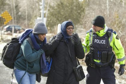 An RCMP officer speaks with women from Sudan after they illegally crossed the Canada-US border near Hemmingford, Quebec