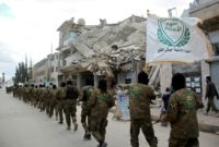 Rebel fighters from the Jaish al-Fatah (Army of Conquest) brigades, which include other rebel factions, parade in the northwestern Syrian city of Idlib