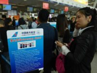 Passengers line up beside a safety warning about the Samsung Galaxy Note 7 smartphone at China's Wuhan airport in this October 2016 file picture