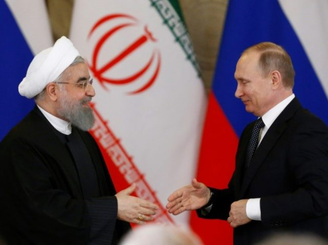 Russian President Vladimir Putin (R) shakes hands with his Iranian counterpart Hassan Rouhani during a joint press conference following their meeting at the Kremlin in Moscow on March 28, 2017