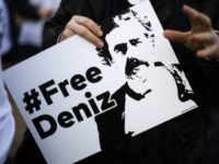 A man holds a poster with the slogan '#FREEDENIZ' during a protest in front of the Turkish embassy in Berlin, Tuesday, Feb. 28, 2017. Demonstrators protest against the police custody of Deniz Yucel, a correspondent in Turkey for the German daily newspaper 'Welt'. (AP Photo/Markus Schreiber)