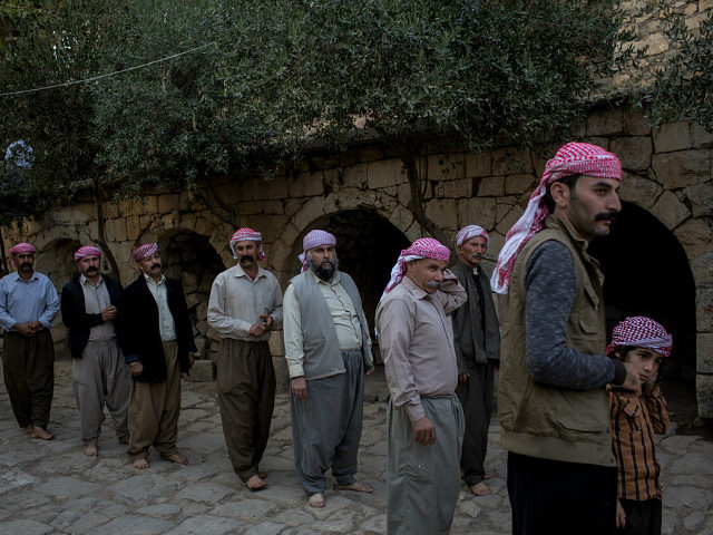 LALISH, IRAQ - NOVEMBER 11: Yazidi men line up before starting a religious ritual outside the holiest temple of the Yazidi faith while attending friday rituals on November 11, 2016 in Lalish, Iraq. Lalish is the site of the tomb of Sheikh Adi ibn Musafir, the central figure of the …