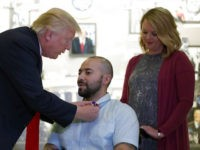 President Donald Trump awards a Purple Heart to U.S. Army Sgt. First Class Alvaro Barrientos, with his wife Tammy Barrientos nearby, at Walter Reed National Military Medical Center, Saturday, April 22, 2017, in Bethesda, Md. (AP Photo/Alex Brandon)