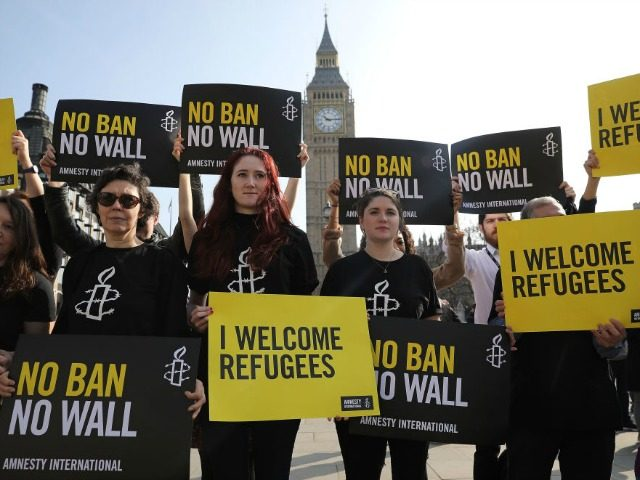Amnesty International activists hold placards as they protest against US President Donald Trump's Travel ban, in Parliament Square on March 16, 2017 in London, England.