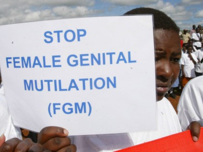A Masai girl holds a protest sign during the anti-Female Genital Mutilation (FGM) run in Kilgoris, Kenya, April 21, 2007. At least 2 million girls every year are at a risk of undergoing FGM. The cut, which is generally done without anesthesia may have lifelong health consequences. (AP Photo/Sayyid Azim)