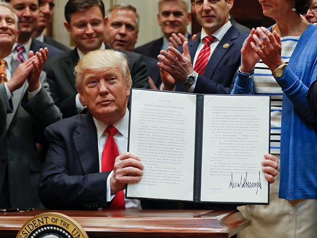 President Donald Trump holds up a signed Executive Order in the Roosevelt Room of the White House in Washington, Friday, April 28, 2017, directing the Interior Department to begin review of restrictive drilling policies for the outer-continental shelf. (AP Photo/Pablo Martinez)