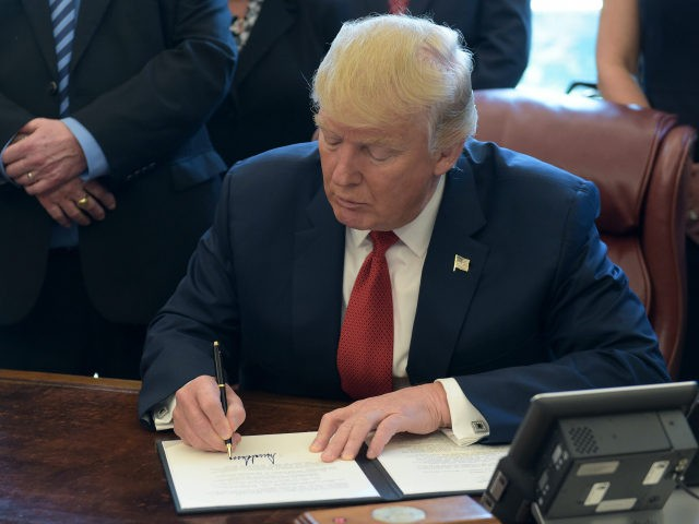 President Donald Trump signs an executive memorandum on investigation of steel imports in the Oval Office of the White House in Washington, Thursday, April 20, 2017. (AP Photo/Susan Walsh)