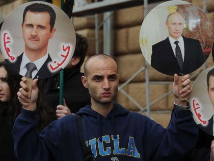 A man holds portrait of Russia's President Vladimir Putin (R) and Syria's President Bashar al-Assad (L) during a rally in support of Syrian regime in front of the US Embassy in Moscow, on October 19, 2012. Moscow has defiantly refused to take sides against Assad, and has slammed the West …