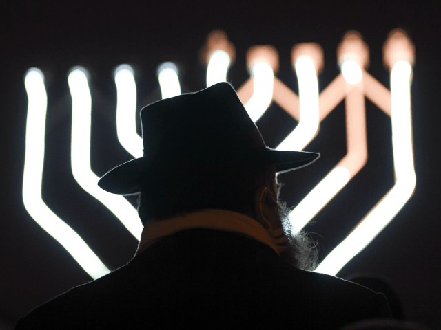 Rabbi Zalman Gurevitch stands in front of a Hanukkah Menorah during the jewish festival of lights at Opernplatz in Frankfurt am Main, western Germany on December 25, 2016. / AFP / dpa / Arne Dedert / Germany OUT (Photo credit should read ARNE DEDERT/AFP/Getty Images)