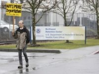 A protester walks past the entrance of the Northwest Detention Center as people attend the Peoples Tribunal Against the Detention Center event organized by undocumented immigrants and formerly detained in Tacoma, Washington on February 26, 2017. / AFP / Jason Redmond (Photo credit should read JASON REDMOND/AFP/Getty Images)