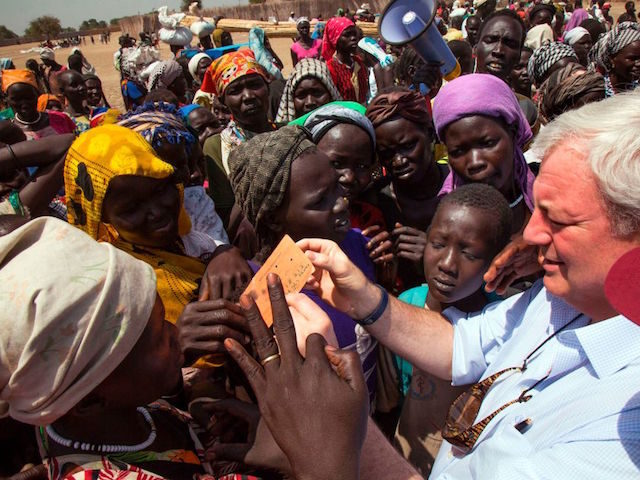 UN Under-Secretary General for Humanitarian Affairs and Emergency Relief Coordinator, Stephen O'Brien (R) checks a beneficiary's ration card for a food distribution on March 4, 2017, in Ganyiel, Panyijiar county, Unity state, in South Sudan. South Sudan was declared the site of the world's first famine in six years, affecting …