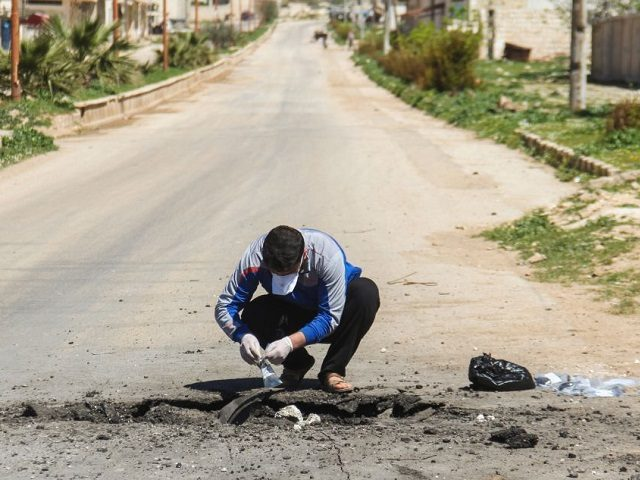 A Syrian man collects samples from the site of a suspected toxic gas attack in Khan Sheikhun, in Syrias northwestern Idlib province, on April 5, 2017. International outrage is mounting over a suspected chemical attack that killed scores of civilians in Khan Sheikhun on April 4, 2017. / AFP PHOTO …