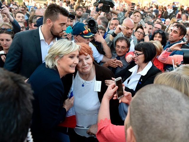 French presidential election candidate for the far-right Front National (FN) party Marine Le Pen (2ndL) poses with a supporter during her campaign rally at the Puybonnieux farm in Pageas, near Limoges, on April 13, 2017. / AFP PHOTO / ALAIN JOCARD (Photo credit should read ALAIN JOCARD/AFP/Getty Images)