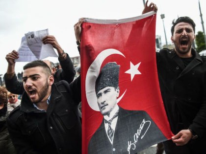 "TOPSHOT - Supporters of the ""No voters"" and members of Turkey's main opposition party, the Republican People's Party (CHP), hold a flag of Mustafa Kemal Ataturk, founder of modern Turkey as they gather at the Caglayan courthourse to submit their petition to object alleged irregularities in Turkish vote on April …"