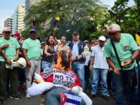 Demonstrators burn an effigy of President Nicolas Maduro during a protest at the east side of Caracas on April 19, 2017.