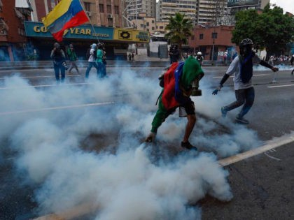 A demonstrator pick up a tear gas canister thrown by the police during a rally against Venezuelan President Nicolas Maduro, in Caracas on April 19, 2017. Venezuela braced for rival demonstrations Wednesday for and against President Nicolas Maduro, whose push to tighten his grip on power has triggered waves of …
