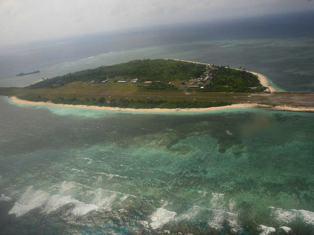 Photographed through the window of a closed aircraft, an aerial view shows Pag-asa Island, part of the disputed Spratly group of islands, in the South China Sea located off the coast of western Philippines on Wednesday July 20, 2011. A group of Filipino lawmakers flew Wednesday to the Philippine-occupied island …