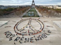 "Environmentalist activists form a human chain representing the peace sign and the spelling out ""100% renewable"", on the side line of the COP21, United Nations Climate Change Conference near the Eiffel Tower in Paris, Sunday, Dec. 6, 2015. Negotiators adopted a draft climate agreement Saturday that was cluttered with brackets …"