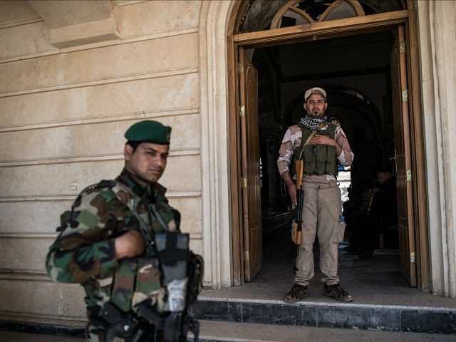 MOSUL, IRAQ - APRIL 16: Syriac Christian militiamen guard Saint John's Church (Mar Yohanna) during an easter ceremony in the nearly deserted predominantly Christian Iraqi town of Qaraqosh on April 16, 2017 near Mosul, Iraq. Qaraqosh was retaken by Iraqi forces in 2016 during the offensive to capture the nearby …