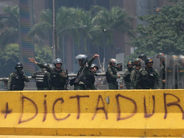 A Venezuelan Bolivarian National Guard officer throws a tear gas grenade towards demonstrators during a protest in Caracas, Venezuela, Monday, April 10, 2017. Thousands of people in Venezuela's capital are protesting against the government of President Nicolas Maduro, demanding new elections and vowing to stay in the streets during the …