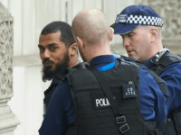 Firearms officiers from the British police detain a man on Whitehall near the Houses of Parliament in central London on April 27, 2017 before being taken away by police.