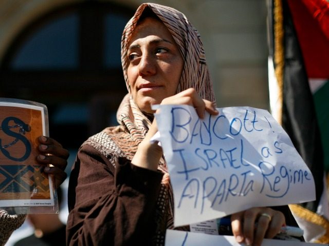 A Palestinian woman hold up a placard reading ' boycott Israel as Aparta regime' as she takes part in an anti-racism demonstration in the center of Geneva, Switzerland, Saturday, April 18, 2009. The United Nations is bracing for a major anti-racism conference here opening next week at its European headquarters, …