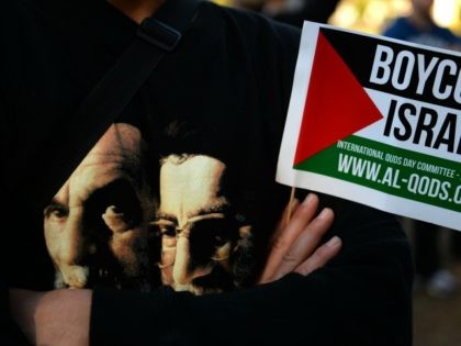 A Demonstrator holds a flag while wearing a t-shirt carrying images of Iranian spritual leader Ayatollah Khomeini (L) and supreme leader Ayatollah Ali Khamenei during a rally to mark Al-Quds day on the last friday of the holy month of Ramadan in Sydney on August 2, 2013. Demonstrators carrying banners …