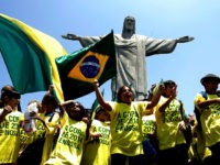 Brazilian schoolboys wave flags and cheer in front of the statue to Christ the Redeemer 30 October, 2007 in Rio de Janeiro, Brazil. Brazil, the only runner in the race, was officially unveiled as the 2014 World Cup host by FIFA president Sepp Blatter in Zurich Tuesday. The five-time world …