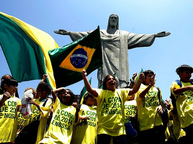 Brazilian schoolboys wave flags and cheer in front of the statue to Christ the Redeemer 30 October, 2007 in Rio de Janeiro, Brazil. Brazil, the only runner in the race, was officially unveiled as the 2014 World Cup host by FIFA president Sepp Blatter in Zurich Tuesday. The five-time world champions have staged the World Cup once before, in 1950, when they lost the final 2-1 to Uruguay in front of a near 200,000 crowd at the Maracana stadium in Rio de Janeiro. AFP PHOTO ANTONIO SCORZA (Photo credit should read ANTONIO SCORZA/AFP/Getty Images)