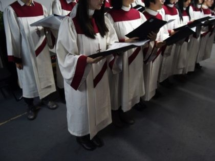 This photo taken on December 24, 2014 shows the choir of an underground church singing at a Christmas Eve service at an apartment in Beijing. China is now home to an estimated 70 million Christians, according to a 2011 survey by the Pew Research Center, as people search for a …