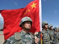 A Chinese soldier holds a Chinese flag during Peace Mission-2016 joint military exercises of the Shanghai Cooperation Organization (SCO) in the Edelweiss training area in Balykchy some 200 km from Bishkek on September 19, 2016. The joint anti-terrorism drill involves more than 1,100 troops of Russia, Kazakhstan, Kyrgyzstan, Tajikistan, Uzbekistan …
