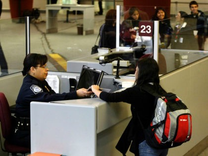 A foreign airline passenger is greeted by a Customs and Border Protection Officer at Hartsfield-Jackson International Airport in Atlanta, Georgia January 5, 2004. REUTERS/Tami Chappell