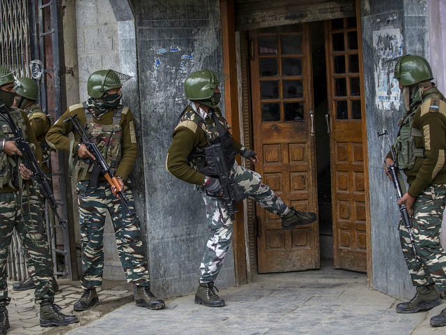 Indian paramilitary soldiers kick open the door of a hotel before entering it, after a suspect was arrested from the hotel, in Srinagar, Indian controlled Kashmir, Saturday, April 1, 2017. Government forces fired in the air and used tear gas to disperse hundreds of youths who came out on the streets after a man, who was suspected to be a rebel, was arrested from the hotel, police said. (AP Photo/Dar Yasin)