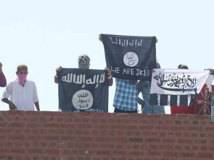 SRINAGAR, INDIA - AUGUST 28: Masked Kashmiri youth hold ISIS, Lashkar-e-Taiba flags and posters of Pakistan founder Mohammad Ali Jinnah and former ISI Chief Hamid and local militant commander of Hizbul Mujahideen Burhan during a protest outside Jamia Masjid in downtown Srinagar, on August 28, 2015 in Srinagar, India. The …
