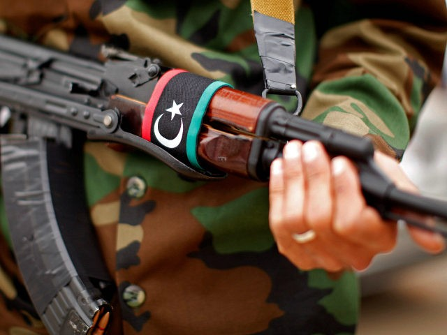 With a Libyan flag on his automatic weapon, a soldier stands guard outside a meeting between U.S. Secretary of State Hillary Rodham Clinton and Libya's Transitional National Council President Mustafa Abdel-Jalil at the World Islamic Call Society Headquarters, during her visit to Tripoli in Libya Tuesday, Oct.18, 2011. (AP Photo …