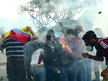 Opposition activists clash with riot police during a protest march in Caracas on April 26, 2017. Protesters in Venezuela plan a high-risk march against President Maduro Wednesday, sparking fears of fresh violence after demonstrations that have left 26 dead in the crisis-wracked country. / AFP PHOTO / RONALDO SCHEMIDT (Photo …