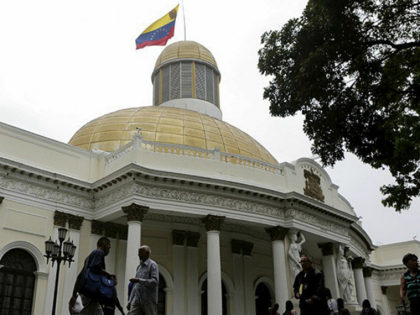 People walk past the National Assembly building during a parliamentary session in Caracas, Venezuela, April 5, 2016.