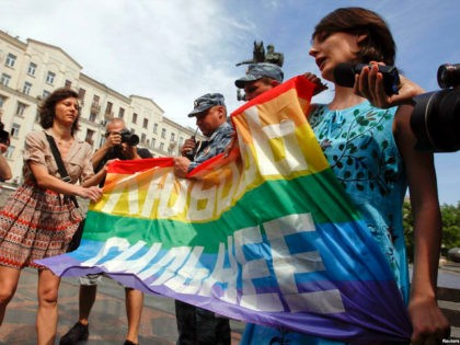 Russian police take away a banner from gay rights activists during a rally outside the mayor's office in Moscow May 25, 2013. The banner reads, 'Love is stronger'. REUTERS/Maxim Shemetov