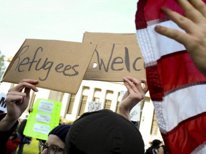 A protester against the United States' acceptance of Syrian refugees uses a U.S. flag to block a counter-protester's sign that read ''Refugees Welcome'' during a demonstration at the Washington State capitol in Olympia, Washington, November 20, 2015. REUTERS/David Ryder