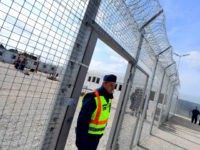 A police officer walks through a gate in at the Tompa border station transit zone on April 6, 2017 as the Hungarian Interior Minister Sandor Pinter (not pictured) presents the camp to the media. The migrant transit complex on the Hungarian side of the border has been expanded to become …