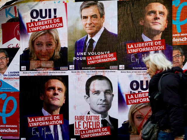 A woman walks past electoral posters of French presidential election candidate for the far-left coalition La France insoumise Jean-Luc Melenchon, French presidential election candidate for the far-right Front National (FN) party Marine Le Pen, French presidential election candidate for the right-wing Les Republicains (LR) party Francois Fillon, French presidential election …